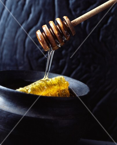 Honey flowing from a spoon onto a honeycomb