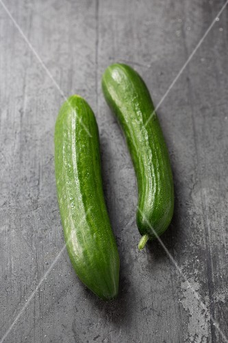Two cucumbers on a grey surface