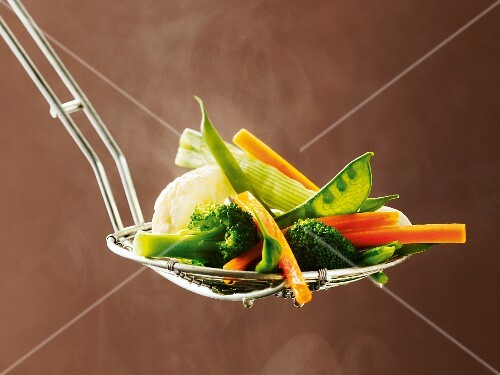 Cooked vegetables on a draining spoon