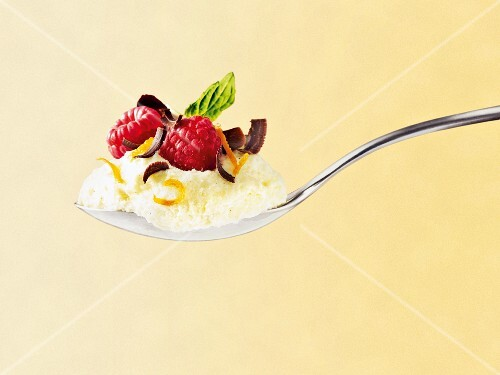 A spoonful of white chocolate mousse with raspberries