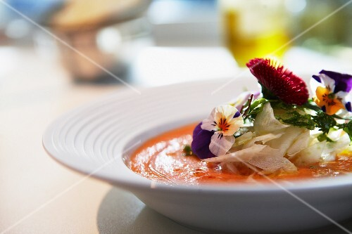 Vegetable soup with edible flowers