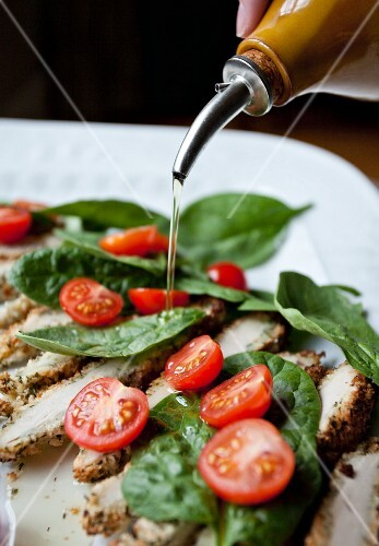 Olive oil being drizzled over chicken, spinach and cherry tomatoes