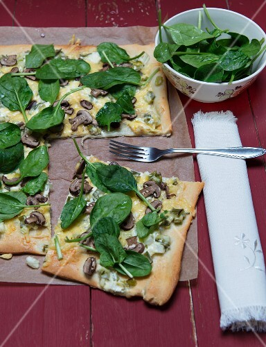 Tarte flambée with mushrooms, spinach and spring onions a piece of baking paper on a red wooden surface