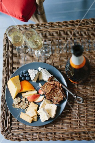 A cheese platter and champagne on a wicker table
