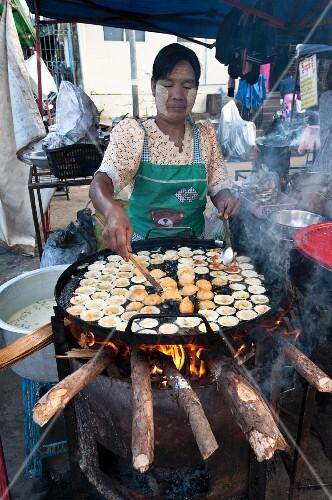 A woman making fritters in a street kitchen (Myanmar, Burma)