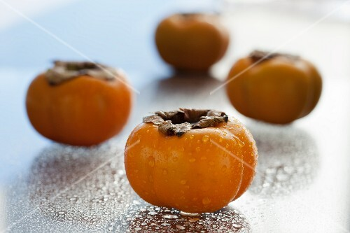 Four persimmons sprayed with water drops
