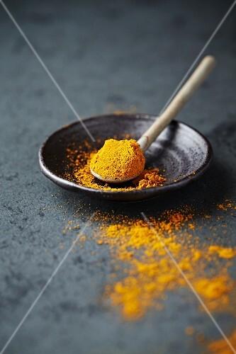 Organic turmeric powder on a ceramic spoon