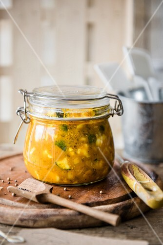 A jar of piccalilli with a wooden spoon