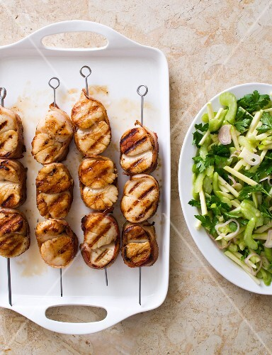 Grilled scallops wrapped in bacon on skewers with a fennel and apple salad