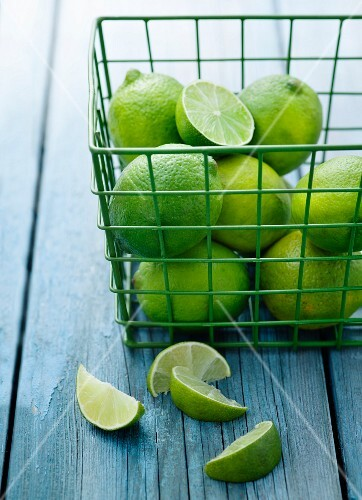 Limes in a green wire basket with lemon wedges in the foreground