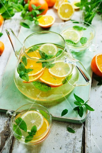 Citrus fruit tea with mint in a glass jug