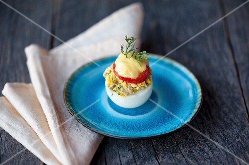 A devilled egg on a blue plate