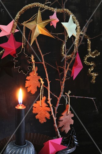 Advent arrangement of chocolate biscuits and stars hung from branch