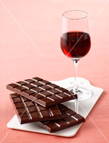 A glass of Barolo and a stacked of chocolate