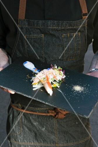 A person holding crab salad on a serving platter (Québec, Canada)