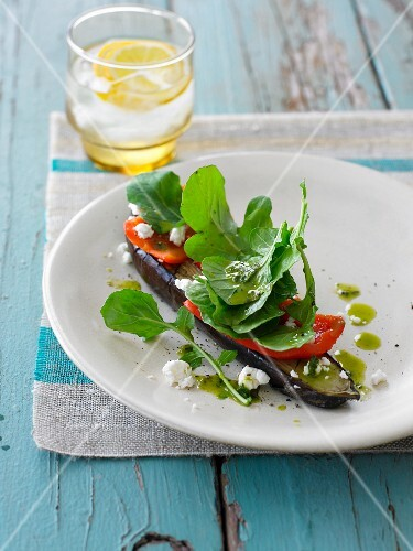 An open aubergine sandwich topped with pepper and feta cheese