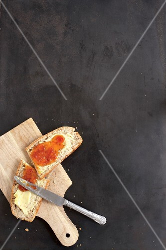 A slice of homemade yeast bread with butter and jam