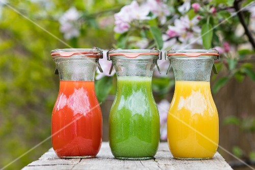 Three chilled vegetable drinks in preserving jars on a table outside