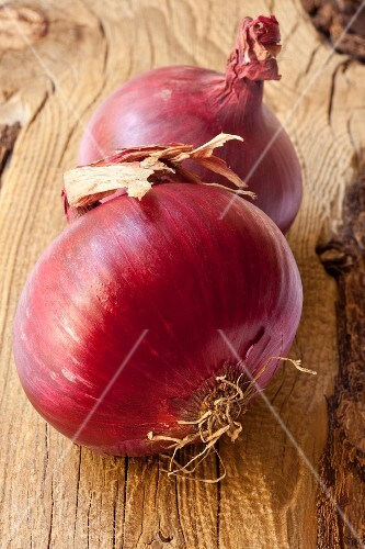 Two red onions on a wooden surface