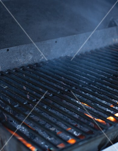 A cooking grid over a smoking charcoal grill
