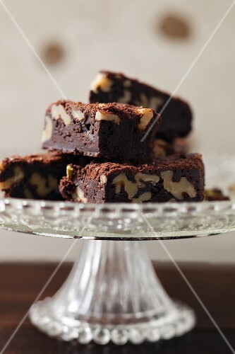 A pile of walnut brownies on a cake stand