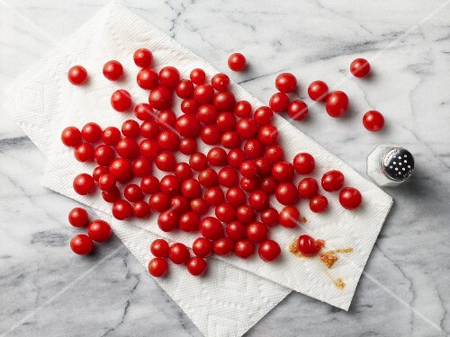 Cherry tomatoes on kitchen paper with a salt shaker