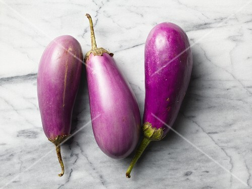 Three aubergines on a marble surface