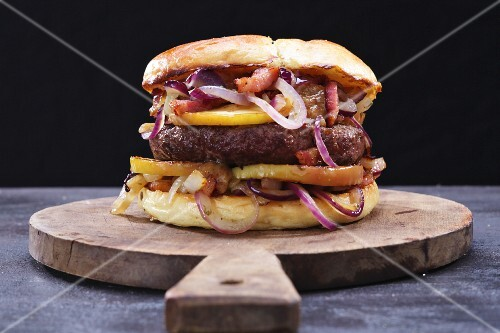 A burger with onions, bacon and apples on a wooden board