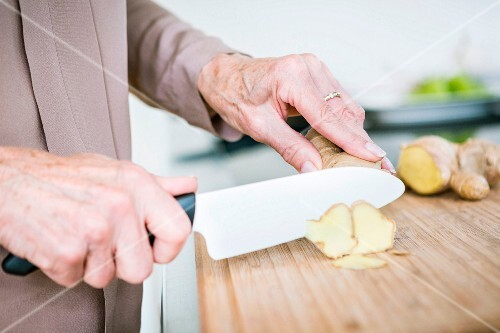 An older woman slicing ginger on a wooden chopping board