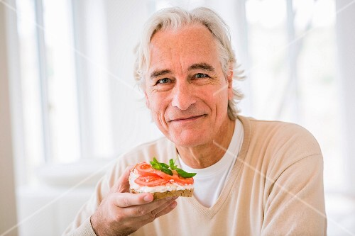 An older man eating a cream cheese and tomato sandwich