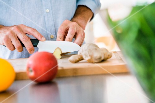 A person chopping ginger on a wooden chopping board