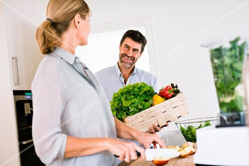 A couple in a kitchen: a man with a crate of vegetables and a woman chopping fruit