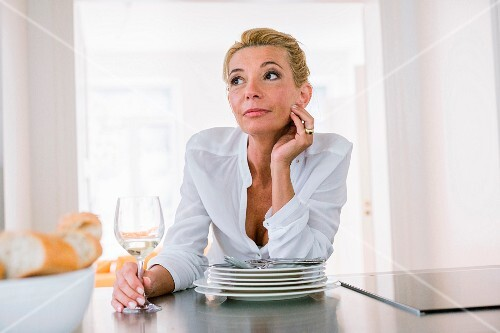 A middle aged woman sitting lost in thought in front of a stack of plates with a glass of wine in the kitchen