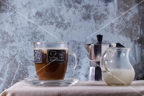 A latte macchiato in a glass cup with a jug of milk and an espresso maker on a white tablecloth