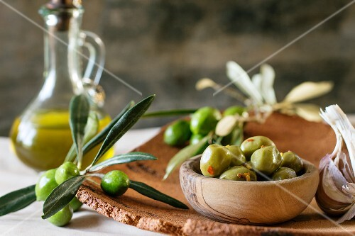 Green marinated olives in olive wood bowl, served with a fresh olive branch and olive oil