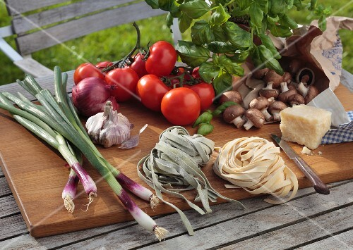Tagliatelle, vegetables, mushrooms, basil and Parmesan on a chopping board