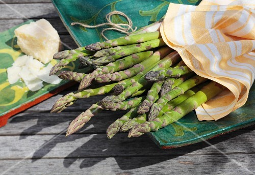 Green asparagus and Parmesan on a garden table