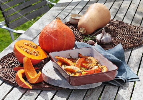 Pumpkin, fresh and roasted, on a garden table