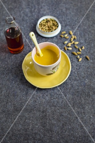 A cup of Vedic milk and a bottle of maple syrup with cardamom pods