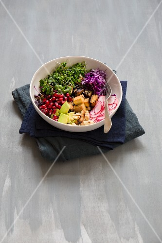 Salad with fried tofu, radishes, red cabbage, pomegranate seeds, avocado, cress and cashew nuts