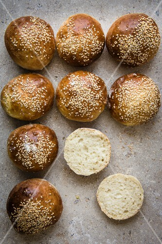 Bread rolls with sesame seeds, one halved