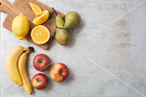 An arrangement of fruit with bananas, orange, lemon, pears and apples