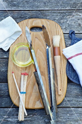 Various grilling utensils on a chopping board