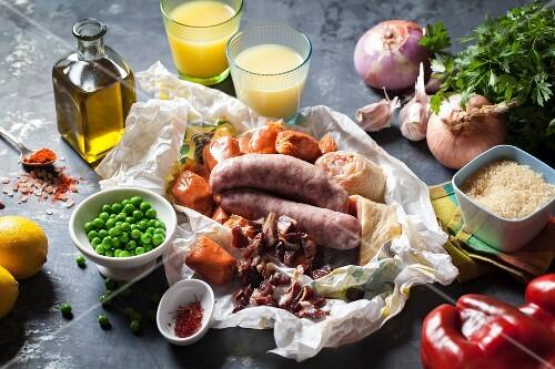 An arrangement of sausage, vegetables, lemon juice and olive oil