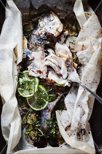 Marinated seabream with limes in parchment paper (bites taken out)
