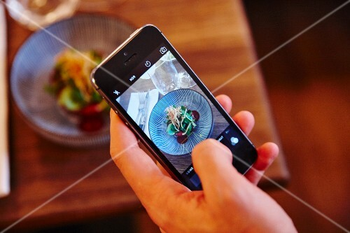 Pictures being taken on a smartphone in a restaurant in Munich