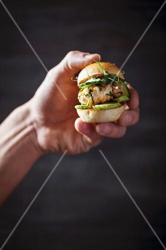 A hand holding a mini fish burger