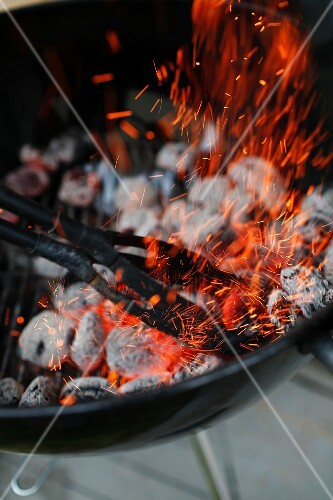 Glowing charcoal being stirred in a barbecue