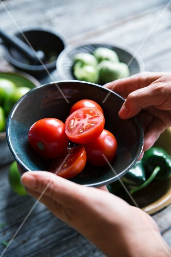 A person holding a bowl of tomatoes with tomatillos and jalapeños in the background