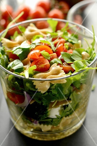 Pasta salad with tomatoes and basil in a glass